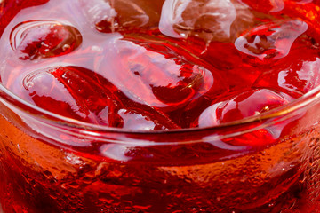 Refreshing: Ice Cubes in a Glass containg Red Drink