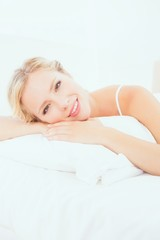 Cheerful young blonde lying on her bed smiling at camera