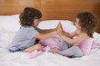 Siblings clapping hands in bed