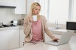 Woman using laptop while drinking coffee in kitchen