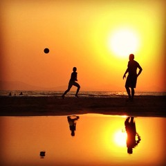 silhouettes playing football at sunset