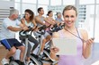 Female trainer with people working out at spinning class