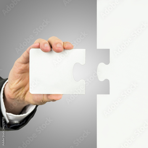 Businessman holding the missing piece of a puzzle