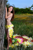 girl in the dress of the firebird of flowers near the tree