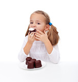 Little girl eating creamy chocolate dessert