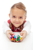 Happy little girl holding colorful modelling clay bars
