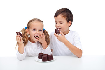 Happy kids eating whipped cream and chocolate dessert