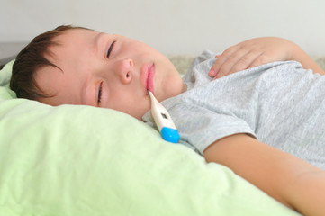 Boy with a thermometer in his mouth lying in bed