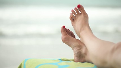 Woman's leg on a sunbed with ocean as background