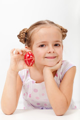Little girl showing a traditional decorated easter egg