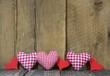 Karierte rote Herzen auf Holz Hintergrund als Grußkarte