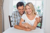 Couple reading text message together at home