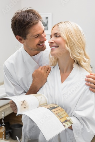 Happy couple with recipe book looking at each other in kitchen