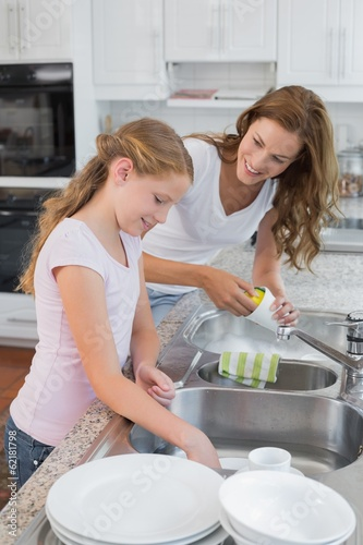 canvas print picture Girl helping her mother to wash utensils in kitchen