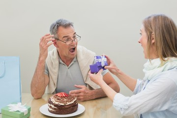 Shocked man receiving a gift by cake on table