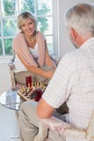 Mature couple playing chess at home