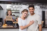 Loving couple with female cafe owner at coffee shop