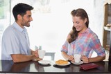 Couple with coffee and croissant at coffee shop