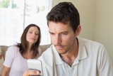 woman looking at man text messaging