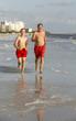 father and son enjoy jogging along the beach