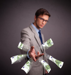 Young man standing and throwing money