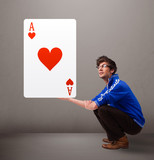 Young man holding a red heart ace