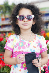pretty little girl standing in sunglasses
