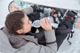 Female snowboarder is drinking for quenching the thirst
