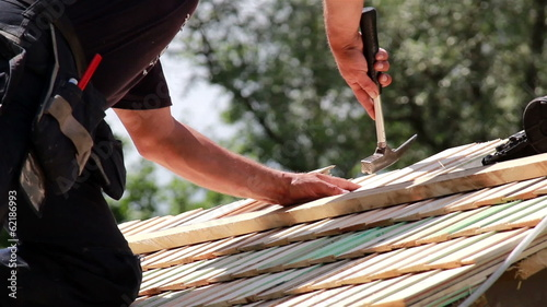 Roofers installing cedar wooden shingle roof
