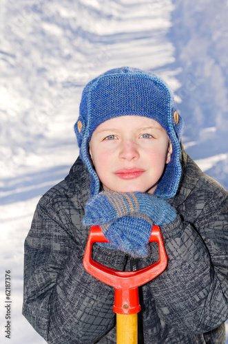 Boy with a shovel after a snow fall.