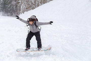 Female snowboarder is jumping on the snow