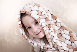 little boy peeking out from under the rug draped over his head
