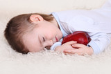 the little boy fell asleep in the arms of an apple