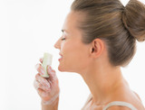 Happy young woman smelling soap