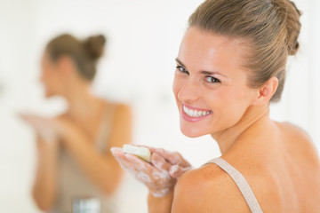 Portrait of smiling young woman washing hands with soap