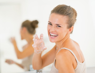 Happy woman having fun time while washing hands in bathroom