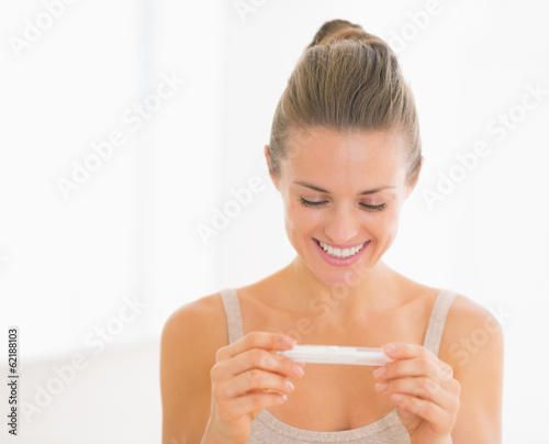 Smiling young woman looking on pregnancy test