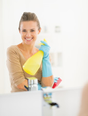Portrait of smiling young housewife in gloves with spray bottle