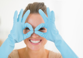 Portrait of happy housewife looking through glasses shaped hands