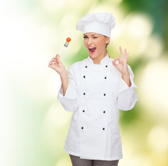 smiling female chef with fork and tomato