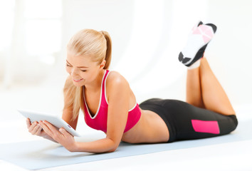 smiling woman lying on the floor with tablet pc
