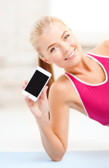 smiling woman lying on the floor with smartphone