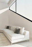 White couch in front of angular window