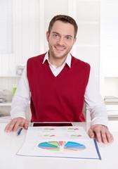 Betriebswirt mit rotem Pullunder lachend im Büro