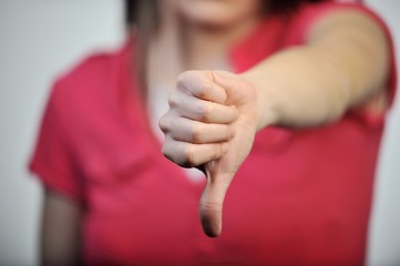 Young business woman gives a thumbs down gesture. Thumb down in