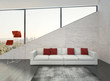 Modern white couch with red pillows against stone wall