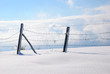 fence with barbed wire in snowy landscape