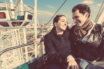 Young Couple having a Ride on a Ferris Wheel