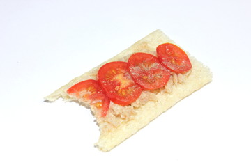Half eaten tuna and tomato crispbread on a white background