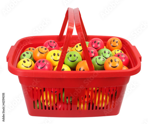 Red shopping basket full of smiley balls